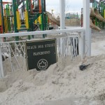 Park sign is covered in sand