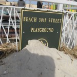Park sign covered in sand (up close)